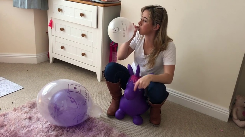 Blowing up a purple balloon inside a balloon on a purple hopper