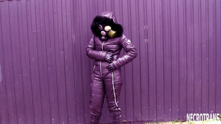 GIRL IN SKI OVERALLS AND GAS MASK.