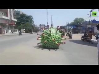 В Индии жителей об опасности предупреждают из автомобиля в форме коронавируса под микроскопом